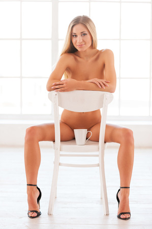 Photo pour Beautiful seductress. Beautiful young naked woman in sitting on the chair and looking at camera  - image libre de droit