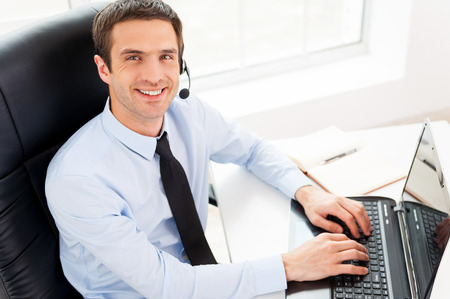 Foto de IT support. Top view of cheerful young man in headset looking at camera and smiling while using laptop - Imagen libre de derechos