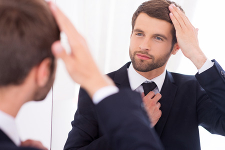 Foto de Making sure he looks perfect. Handsome young man in formalwear adjusting his hairstyle and smiling while standing against mirror - Imagen libre de derechos