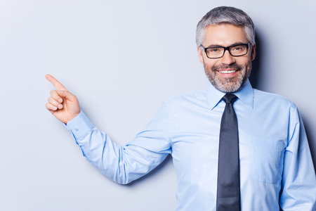 Foto de Businessman pointing copy space. Happy mature man in shirt and tie looking at camera and pointing away while standing against grey background - Imagen libre de derechos
