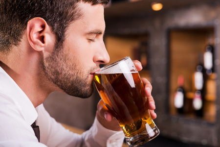 Photo pour Man drinking beer. Side view of handsome young man drinking beer while sitting at the bar counter  - image libre de droit