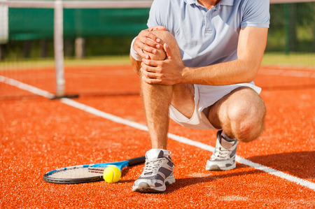 Foto per Sports injury. Close-up of tennis player touching his knee while sitting on the tennis court - Immagine Royalty Free