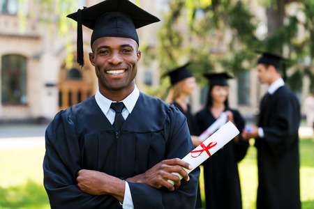 Photo pour Happy graduate. Happy African man in graduation gowns holding diploma and smiling while his friends standing in the background  - image libre de droit