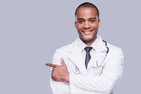 Photo for Confident male doctor. Cheerful African doctor pointing away and smiling while standing against grey background - Royalty Free Image
