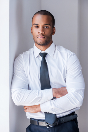 Photo for Successful businessman. Handsome young African man in shirt and tie looking at camera and keeping arms crossed while leaning at the wall - Royalty Free Image