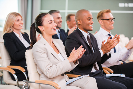 Foto de Applauding to speaker. Group of happy business people in formalwear sitting at the chairs in conference hall and applauding  - Imagen libre de derechos