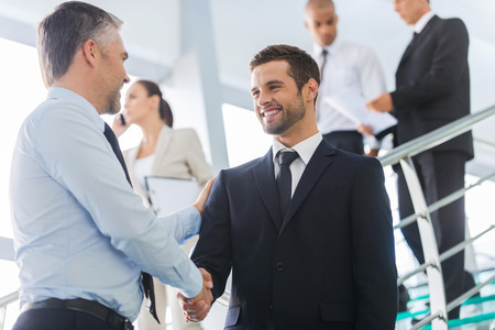 Photo for Businessmen shaking hands. Two confident businessmen shaking hands and smiling while standing at the staircase together with people in the background  - Royalty Free Image