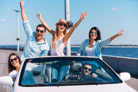 Photo pour Spending great time in convertible. Group of young happy people enjoying road trip in their white convertible and raising their arms - image libre de droit