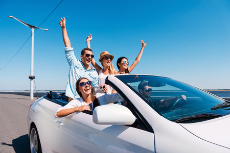 Photo pour Nothing but friends and road ahead. Group of young happy people enjoying road trip in their white convertible and raising their arms up - image libre de droit