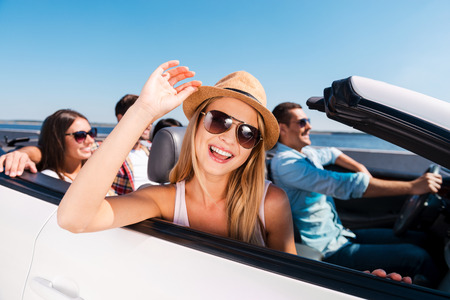 Photo pour Enjoying road trip. Group of young happy people enjoying road trip in their white convertible - image libre de droit