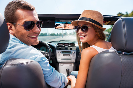 Foto de Enjoying road trip together. Beautiful young couple enjoying road trip in their convertible and looking over shoulder with smile - Imagen libre de derechos