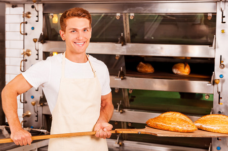 Fresh baked bread for you. Confident young man in apron taking fresh baked bread from oven and smiling