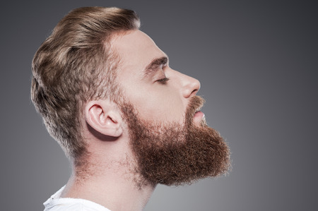 Foto de Bearded handsome. Side view of handsome young bearded man keeping eyes closed while standing against grey background - Imagen libre de derechos