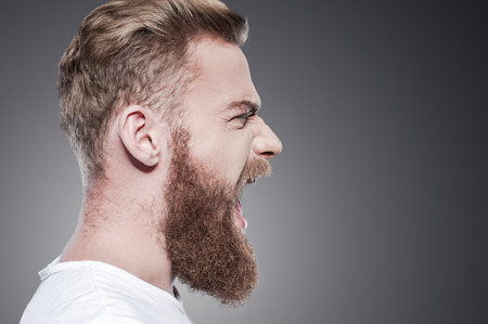 Foto de Unleashing his emotions. Side view of furious young bearded man shouting while standing against grey background - Imagen libre de derechos