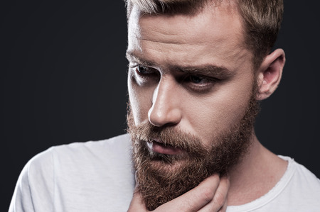 Foto de Lost in thoughts. Portrait of thoughtful young bearded man looking away and holding hand on chin while standing against grey background - Imagen libre de derechos