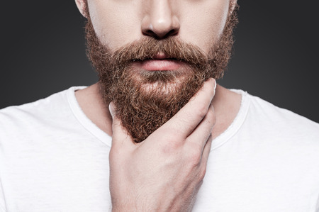 Photo pour Touching his perfect beard. Close-up of young bearded man touching his beard while standing against grey background - image libre de droit