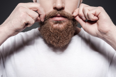 Foto de Making his own style. Close-up of young bearded man adjusting his mustaches while standing against grey background - Imagen libre de derechos