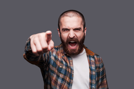 Foto de Hey you! Furious young bearded man pointing you and shouting while standing against grey background - Imagen libre de derechos