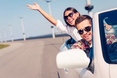 Photo pour Fun ride. Happy young couple enjoying road trip in their white convertible - image libre de droit