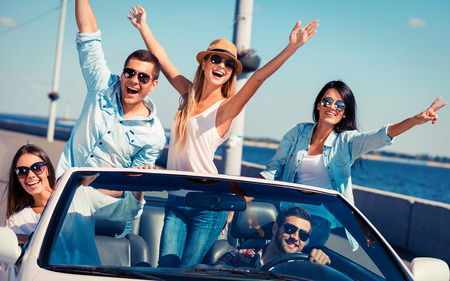 Foto de Friends in convertible. Group of young happy people enjoying road trip in their white convertible and raising their arms - Imagen libre de derechos