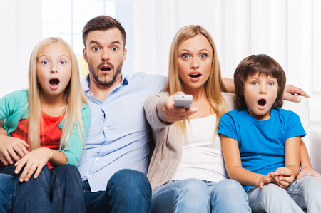 Foto de That is just amazing! Surprised family of four bonding to each other and keeping mouth open while watching TV at home together - Imagen libre de derechos
