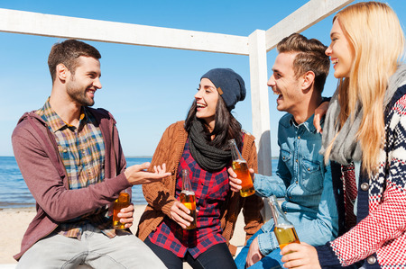 Photo for Young and carefree. Four happy friends talking to each other and smiling while sitting on the beach and drinking beer - Royalty Free Image