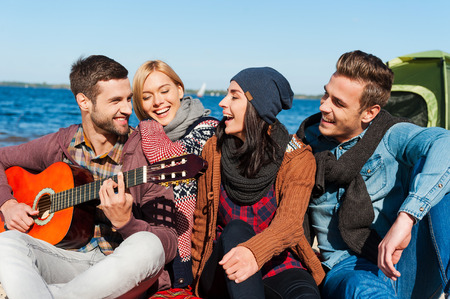 Photo for Just friends and guitar. Group of young cheerful people sitting at the riverbank together while young handsome man playing guitar and smiling - Royalty Free Image