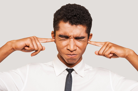 This is too loud! Frustrated young Afro-American man in formalwear plugging ears with his fingers and keeping eyes closed while standing against grey background