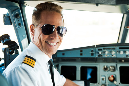 Photo pour Pilot in cockpit. Rear view of confident male pilot looking over shoulder and smiling while sitting in cockpit - image libre de droit