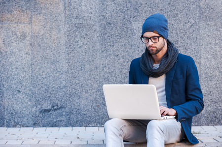 Foto de Surfing the net outdoors. Handsome young man in smart casual wear working on laptop while sitting outdoors - Imagen libre de derechos