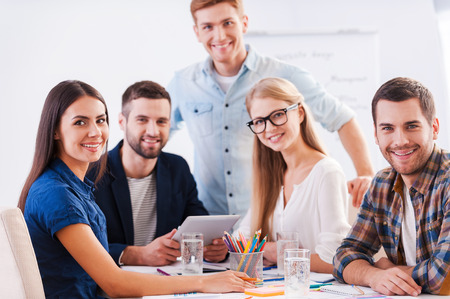 Foto de Ready to brainstorm. Group of happy business people in smart casual wear sitting together at the table and looking at camera - Imagen libre de derechos