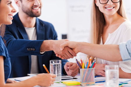 Photo for Congratulations! Close-up of business people in smart casual wear shaking hands and smiling while sitting at the table together - Royalty Free Image