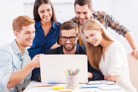 Foto de Brainstorm. Group of cheerful business people in smart casual wear looking at the laptop together and smiling - Imagen libre de derechos
