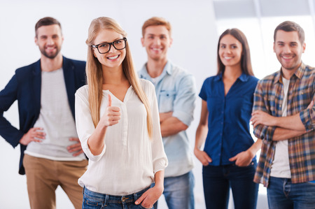 Photo pour Join a successful team! Beautiful young woman showing her thumb up and smiling while group of happy young people standing  - image libre de droit