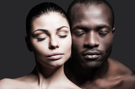 Face to face. Portrait of shirtless African man and Caucasian woman bonding their faces to each other and keeping eyes closed while standing against grey background
