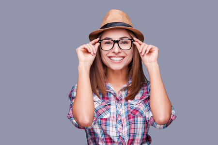 Foto de Funky style beauty. Portrait of beautiful young woman in glasses and funky hat adjusting her glasses and smiling while standing against grey background - Imagen libre de derechos