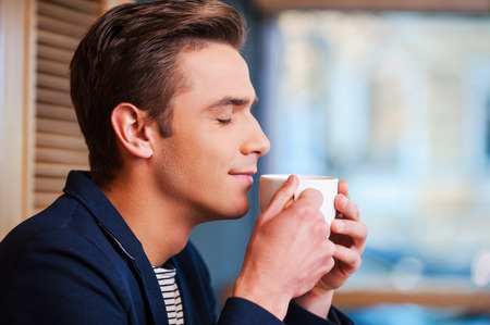 Foto de Enjoying the best coffee in town. Side view of handsome young man keeping eyes closed and smiling while smelling cup of fresh coffee in cafe - Imagen libre de derechos