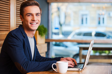 Photo for No minute without my laptop. Handsome young man working on laptop and smiling while enjoying coffee in cafe - Royalty Free Image