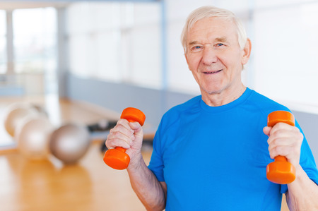 Photo pour On the road to recovery. Happy senior man exercising with dumbbells and smiling while standing indoors - image libre de droit