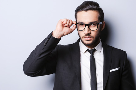 Photo pour Taking life seriously. Portrait of handsome young man in formal wear adjusting his glasses while standing against grey  - image libre de droit