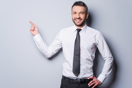 Photo pour Copy space at his hand. Happy mature man in shirt and tie pointing copy space and smiling while standing against grey background - image libre de droit