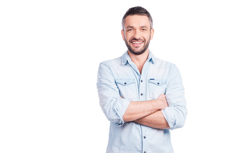 Foto de Charming handsome. Handsome young man in casual wear keeping arms crossed and smiling while standing isolated on white background - Imagen libre de derechos
