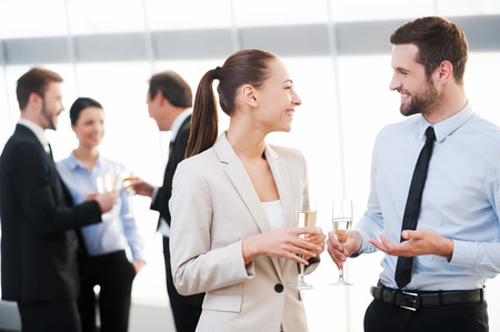 Foto de Celebrating their common success. Two cheerful business people drinking champagne and talking while other people communicating in the background - Imagen libre de derechos
