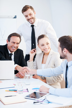Photo pour Congratulations! Two confident businessmen handshaking and smiling while sitting at the table together with their colleagues - image libre de droit