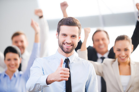 Photo pour Feeling confident in his team. Happy businessman showing his thumb up and smiling while his colleagues standing in the background - image libre de droit