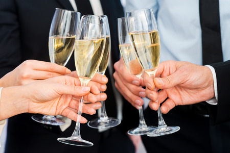Photo for Cheers to success. Close-up of business people holding flutes with champagne - Royalty Free Image