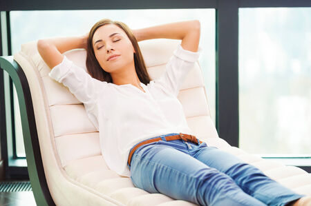 Foto de Total relaxation. Beautiful young woman holding hands behind head while sleeping on the couch - Imagen libre de derechos