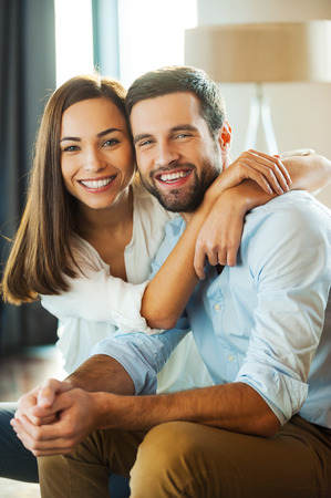 Photo pour Happy to be together. Beautiful young loving couple sitting together on the couch while woman embracing her boyfriend and smiling - image libre de droit