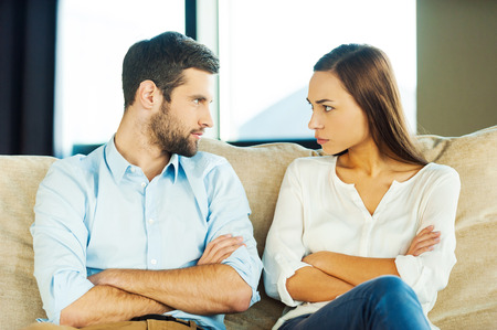 Photo for It is your fault! Angry young couple looking at each other and keeping arms crossed while sitting close to each other on the couch - Royalty Free Image