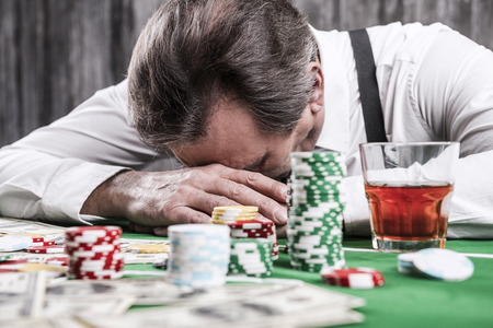 Foto de It is not my day. Depressed senior man in shirt and suspenders leaning his head at the poker table with money and gambling chips laying all around him - Imagen libre de derechos